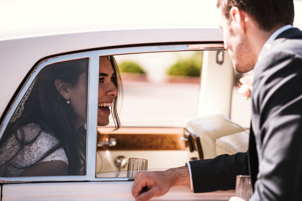 Groom chats with his new bride through the window of a classic Rolls Royce.