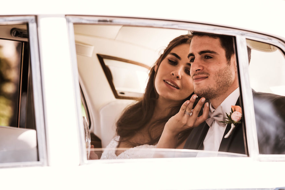 Newlywed couple has a tender moment alone in the a classic car as they head off to their wedding reception at the Darlington House in La Jolla.