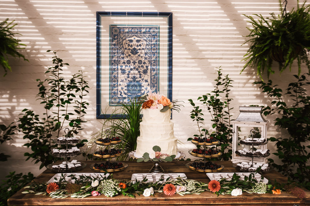 Simple tiered white wedding cake and dessert table with floral details.