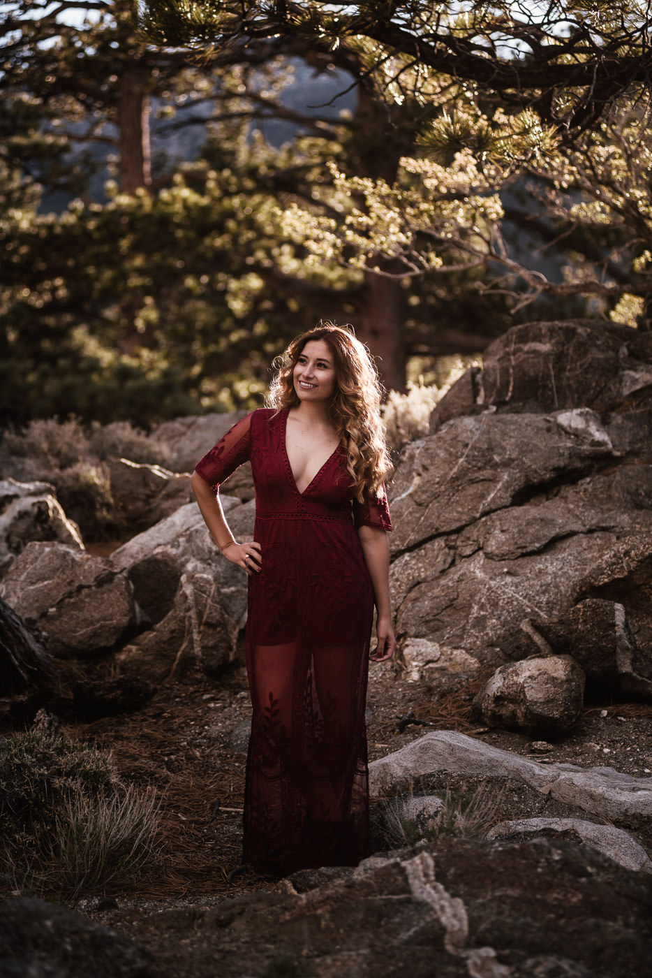 Beautiful bride to be poses in her red engagement dress.
