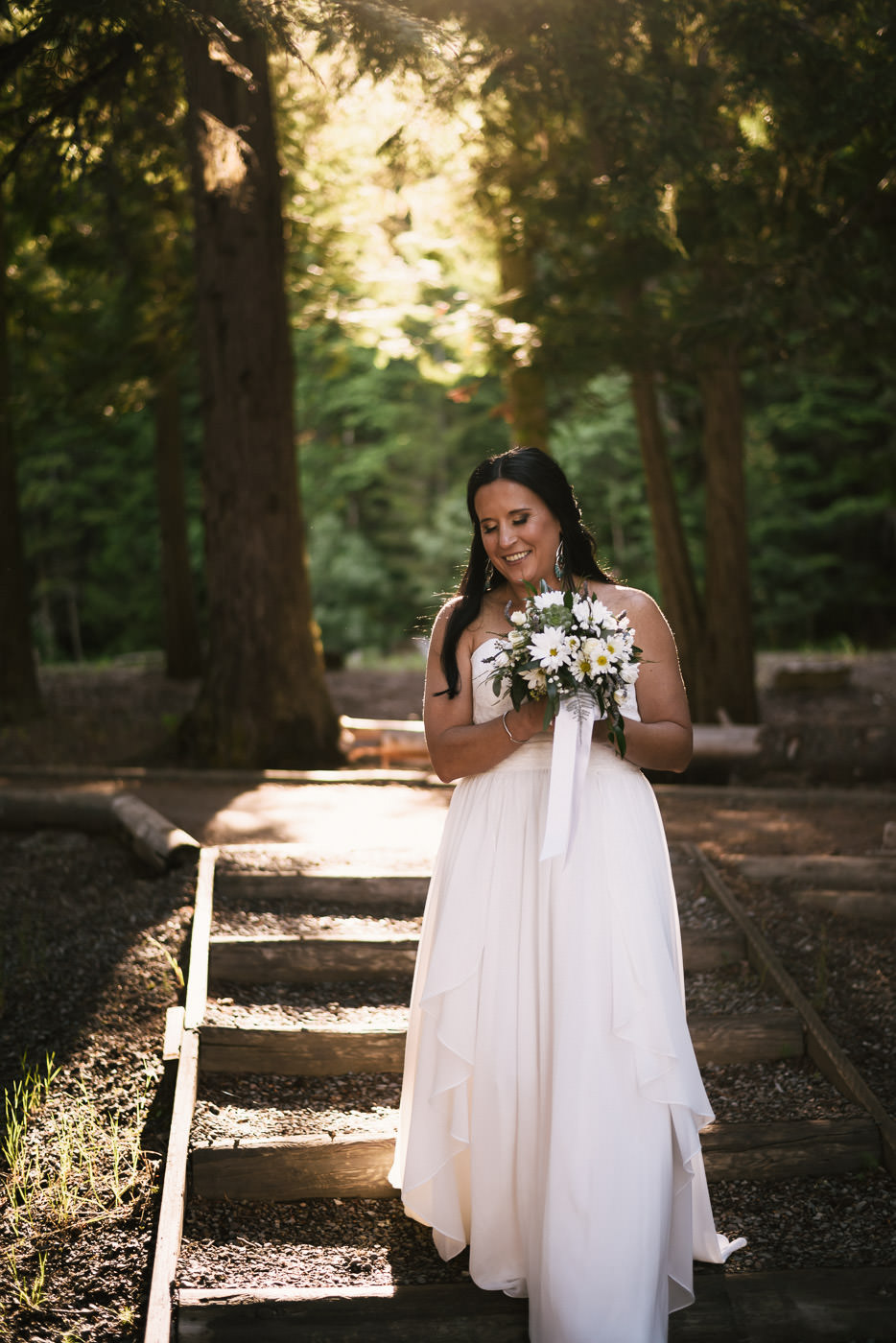 Bride walks down the path to her wedding ceremony at Lake Mcdonald.