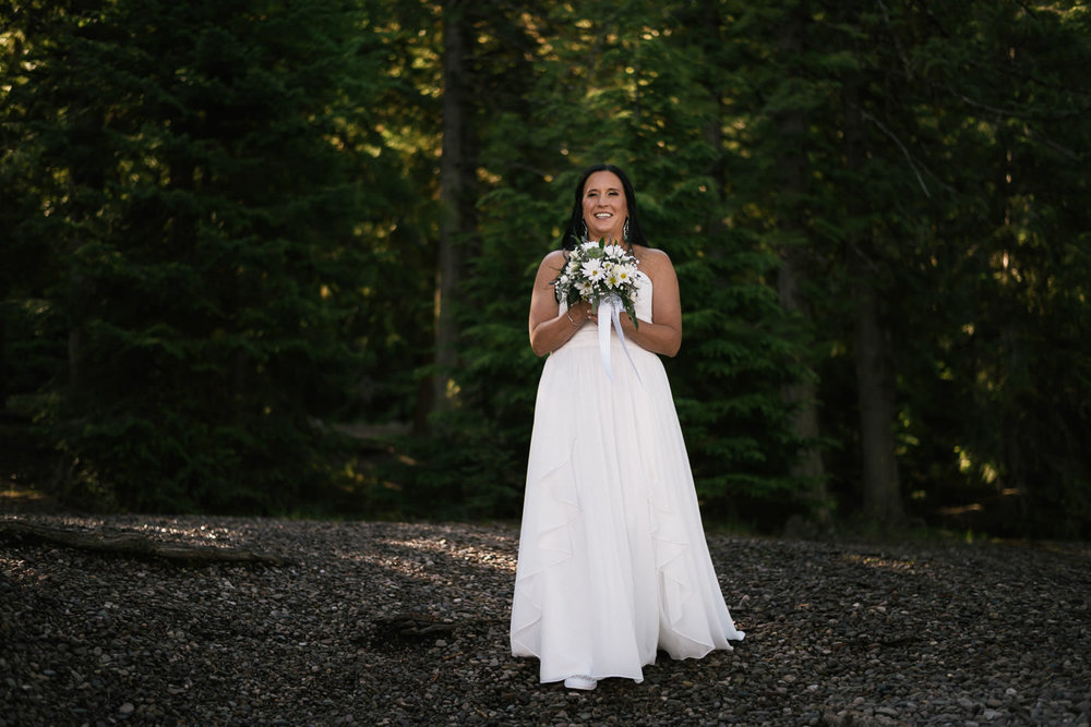 Bride is all smiles as she sees her new husband on the shores of Lake McDonald for their adventurous elopement.