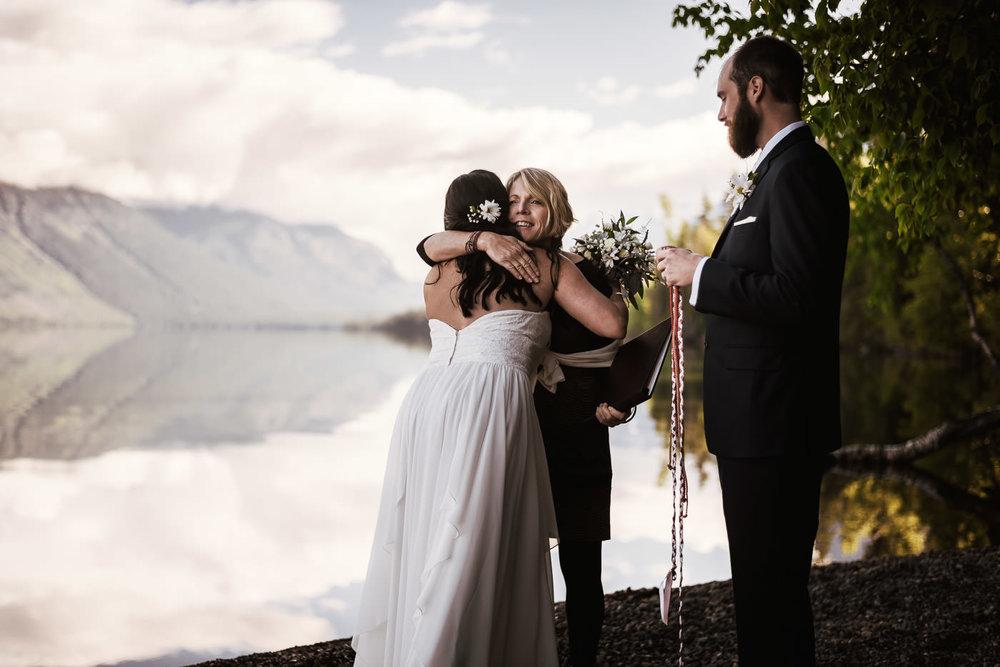 Wedding Officant Sally Hanger hugs the newlyweds in Montana.