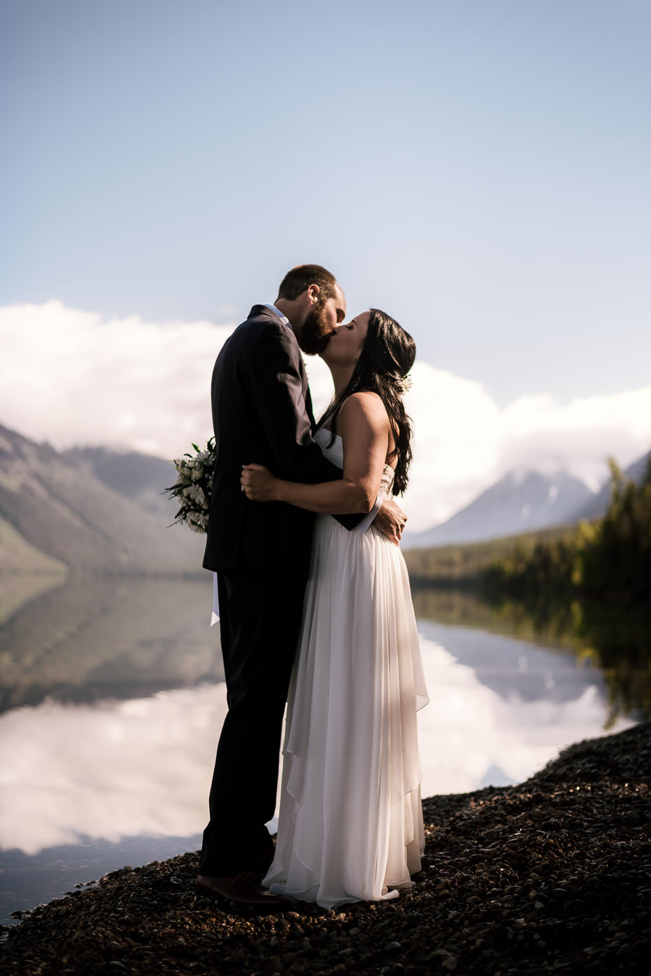 Newlyweds kiss on the gravel shoreline of Lake Mcdonald in Montana.
