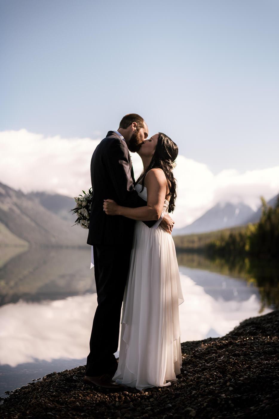 Newlyweds kiss on the gravel shoreline of Lake Mcdonald in Montana.