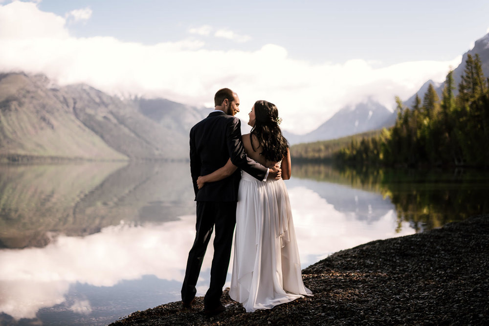 "Storms and a Sunrise ceremony on Lake Mcdonald - Glacier National Park had been on the top of my travel list for sometime now. So when Katie's email came in with the subject ""Glacier National Park elopement"", I was absolutely thrilled and boy did it live up to the hype. Glacier truly is the ""crown of the continent"" and, as I found out, as wild as it is beautiful. I arrived a few days early to scout things out and was met with strong winds, hail, and torrential rain. I woke the morning of the ceremony a little worried, but the skies cleared and gave us perfect weather for adventuring and creating beautiful photos. To start things off these two love birds tied the knot on the shores of the beautiful, and crystal clear Lake McDonald just after sunrise. It was intimate, and breathtakingly beautiful. A moment these two will never forget."