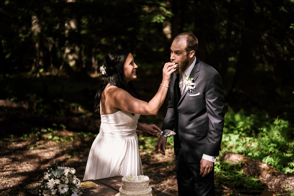Bride feeds her new husband a piece of wedding cake.