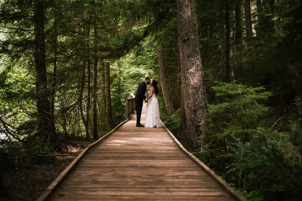 Couples stops for a kiss while hiking the trail of cedars in Montana.