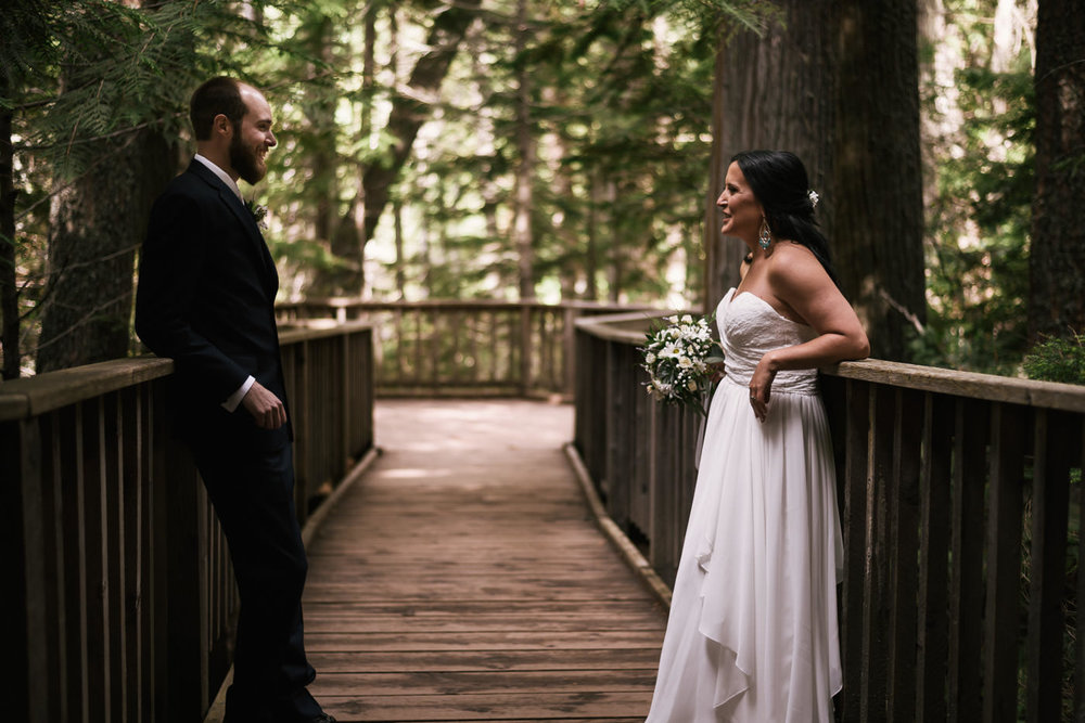 Bride and groom lean back for a casual photo among the cedars.