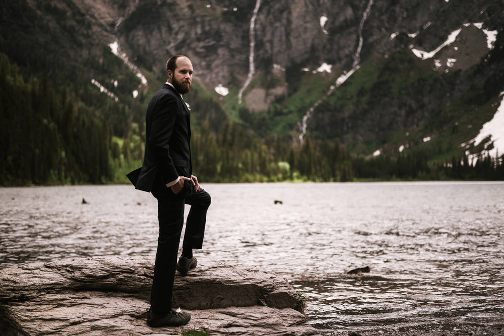 Groom stands upon a rock beside Avalanche Lake in Glacier National Park.