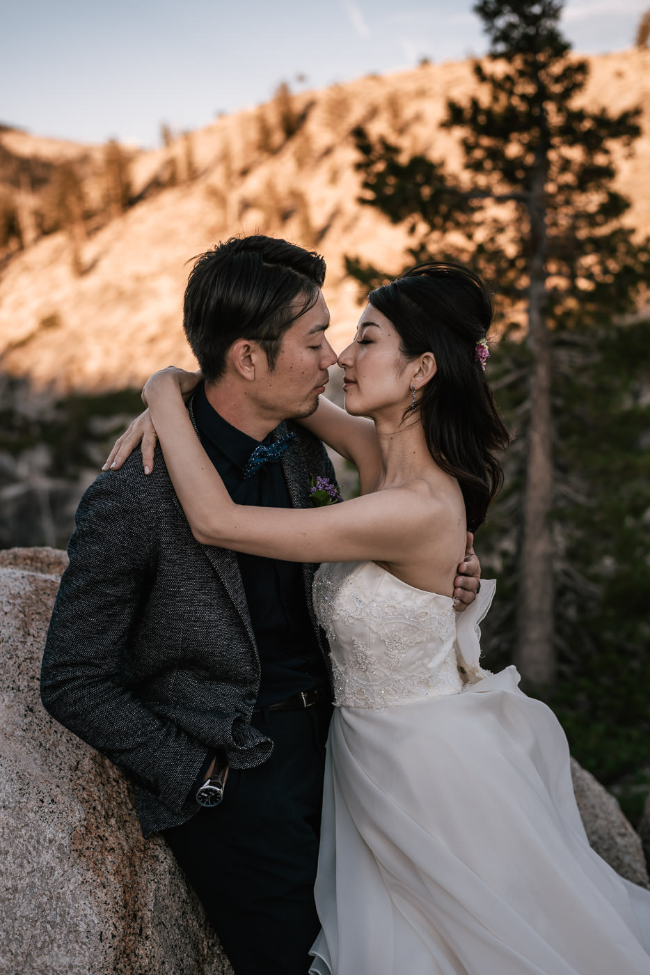Newlyweds get nose to nose for an intimate embrace atop a mountain in the National Parks of the United States.