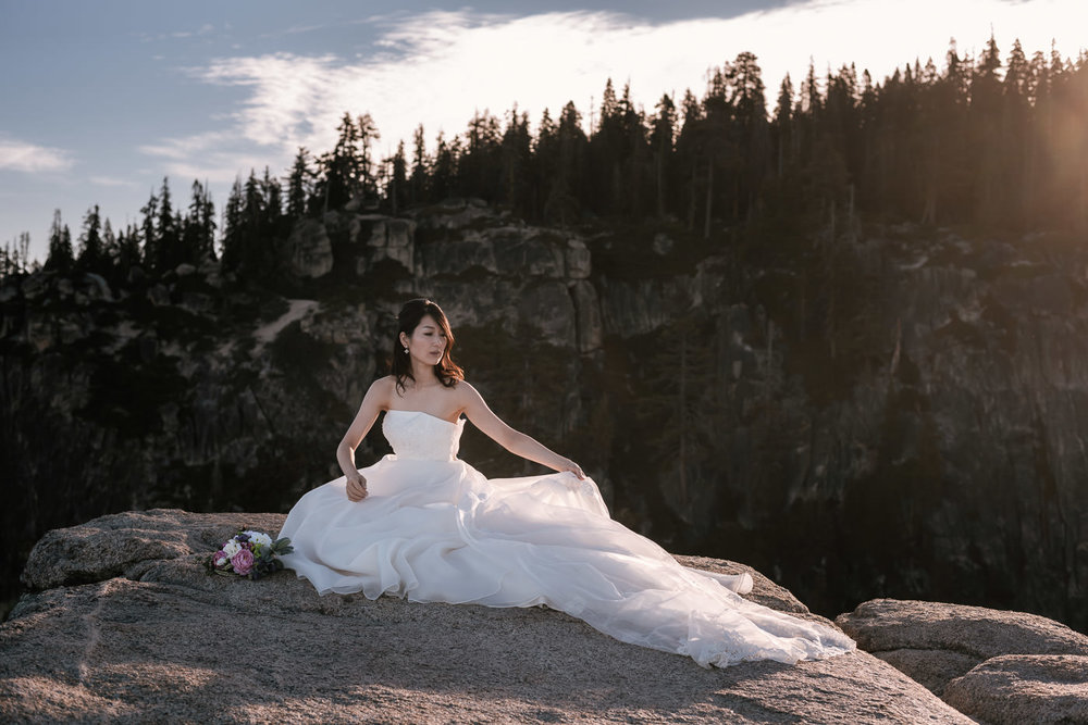 Bride fixes dress for a stunning portrait at sunrise at Taft Point in Yosemite National Park, California.