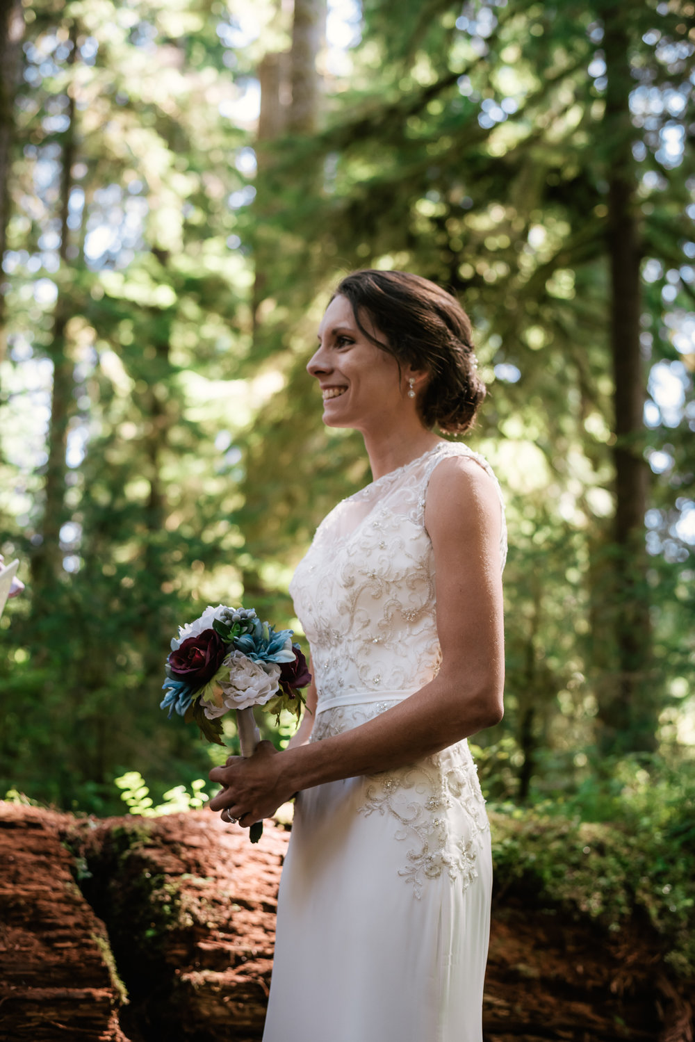 Bride smiles at her groom as he reads his wedding vows in the Hoh Rainforest.