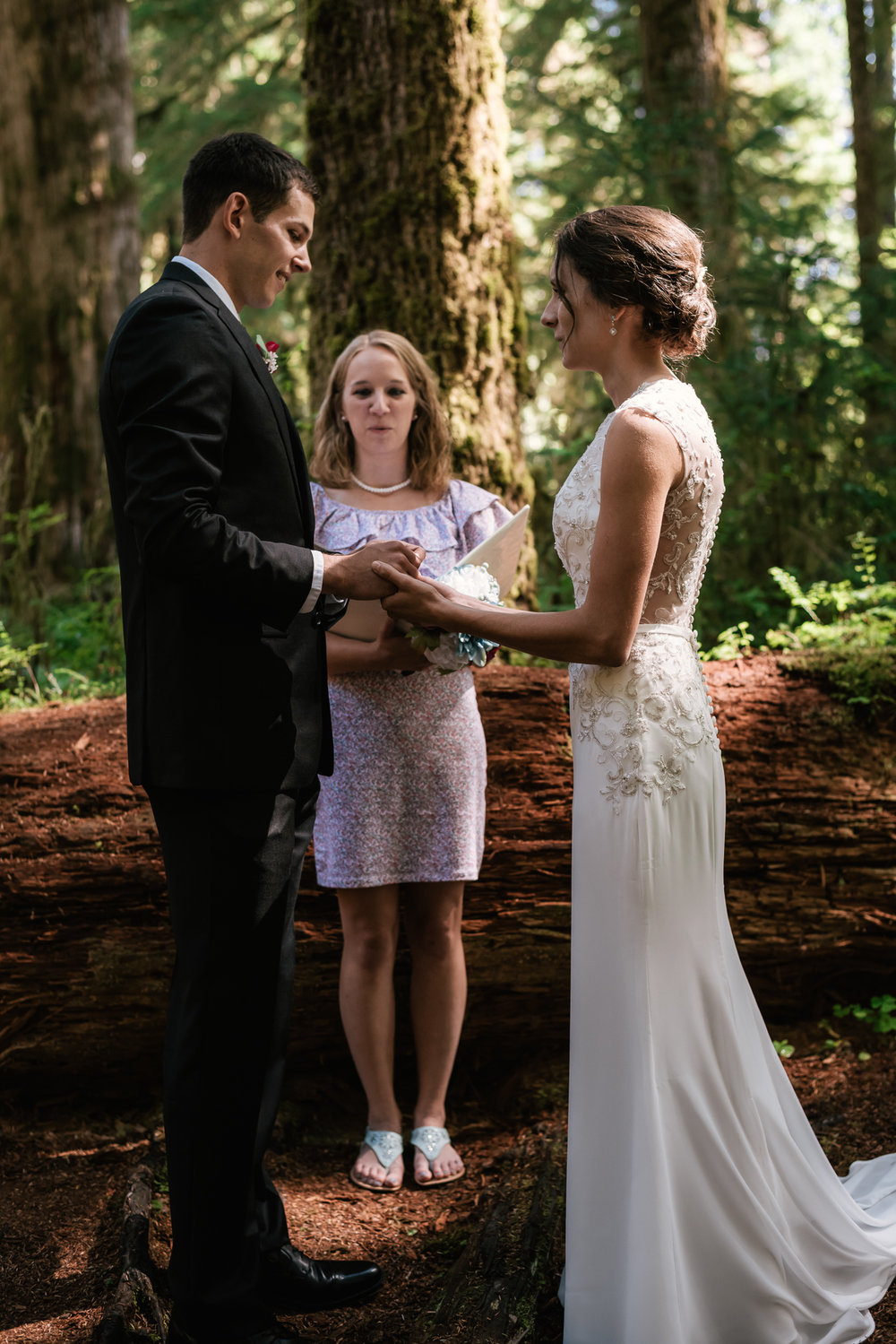 Groom holds his brides hands as he says I do beneath the canopy of cedar trees in Olympic National Park.