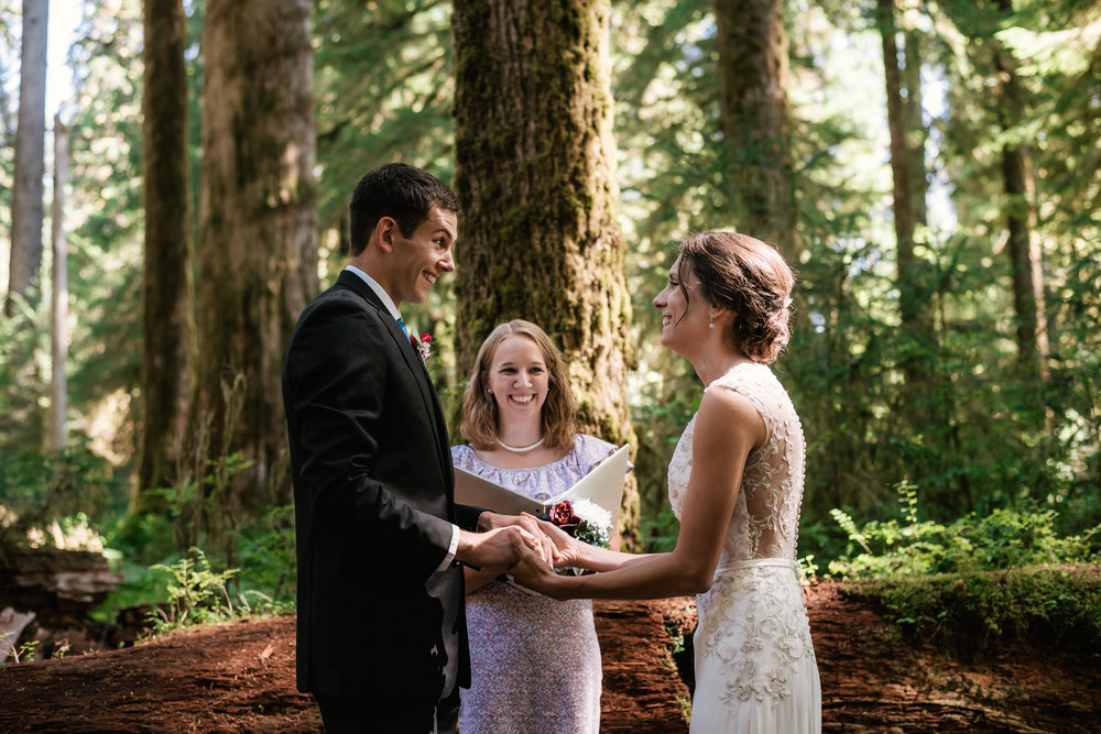 Couple looks at one another and smiles as they finish their marriage ceremony during their Olympic National Park elopement.