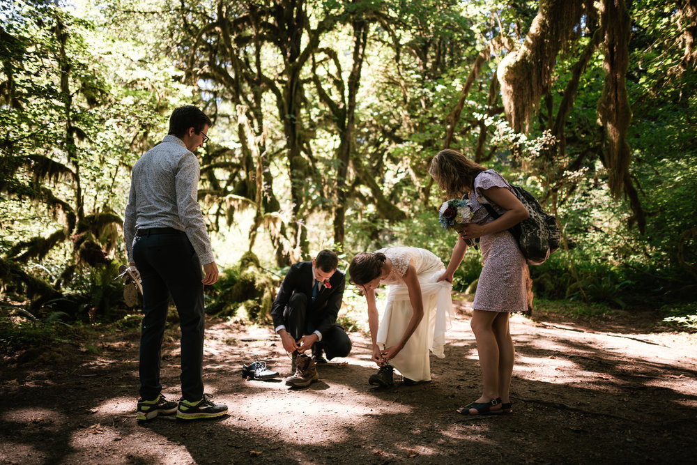 Couple pauses for a moment to switch their shoes for a short hike in their wedding attire.
