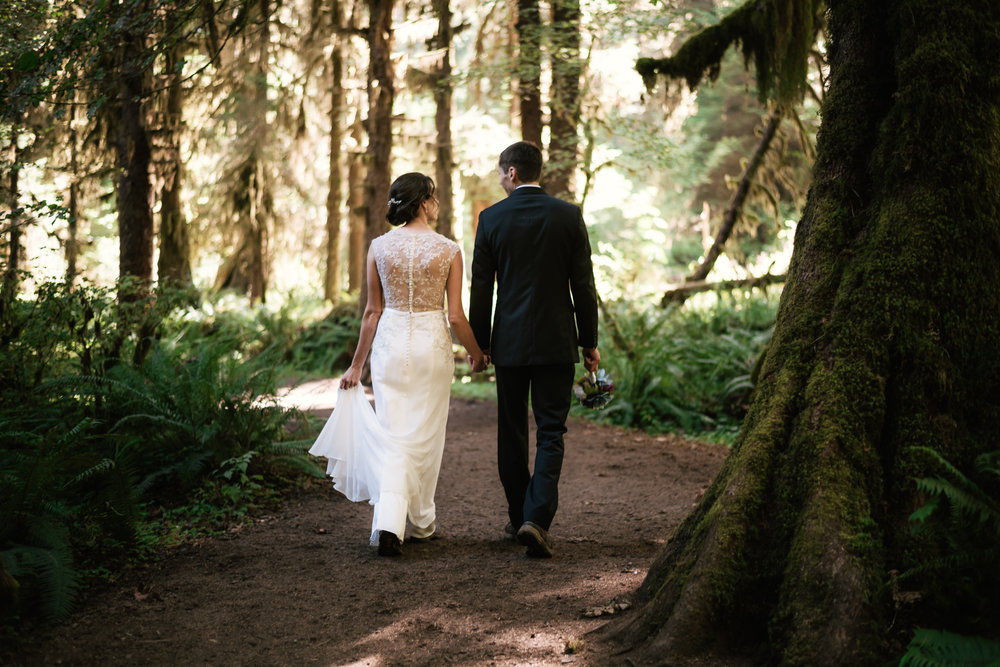 Two newlyweds take a romantic stroll through the ferns and trees of the Hoh Rainforest during their elopement.