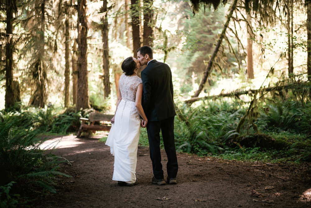 Eloping couple stops for a kiss during their hike through the Hoh Rainforest.