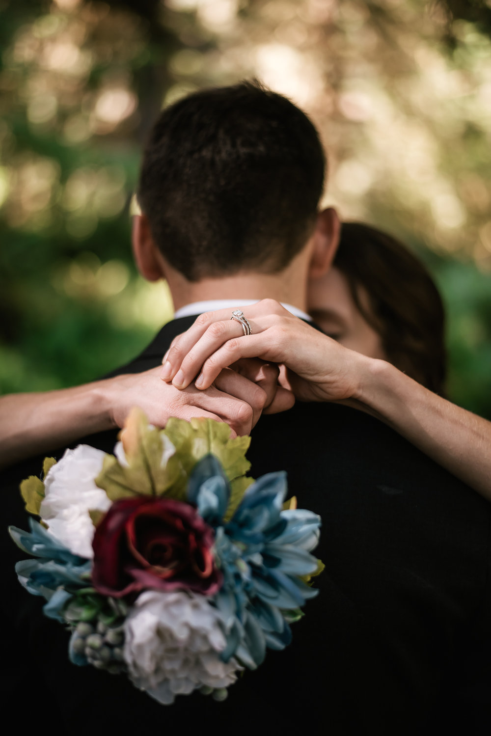 Bride wraps her arms around her husband and shows off her engagement ring and bouquet.