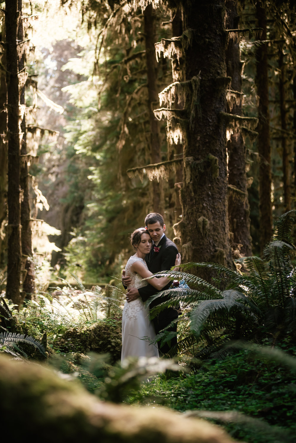 Newlyweds tender embrace among the greenery of the Pacific Northwest.