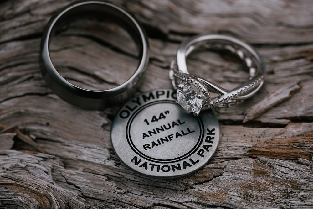 Couples diamond wedding rings with a national park coin from their elopement destination.