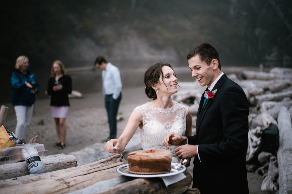 Couple prepares to cut their wedding cake on a driftwood table at Ruby Beach.