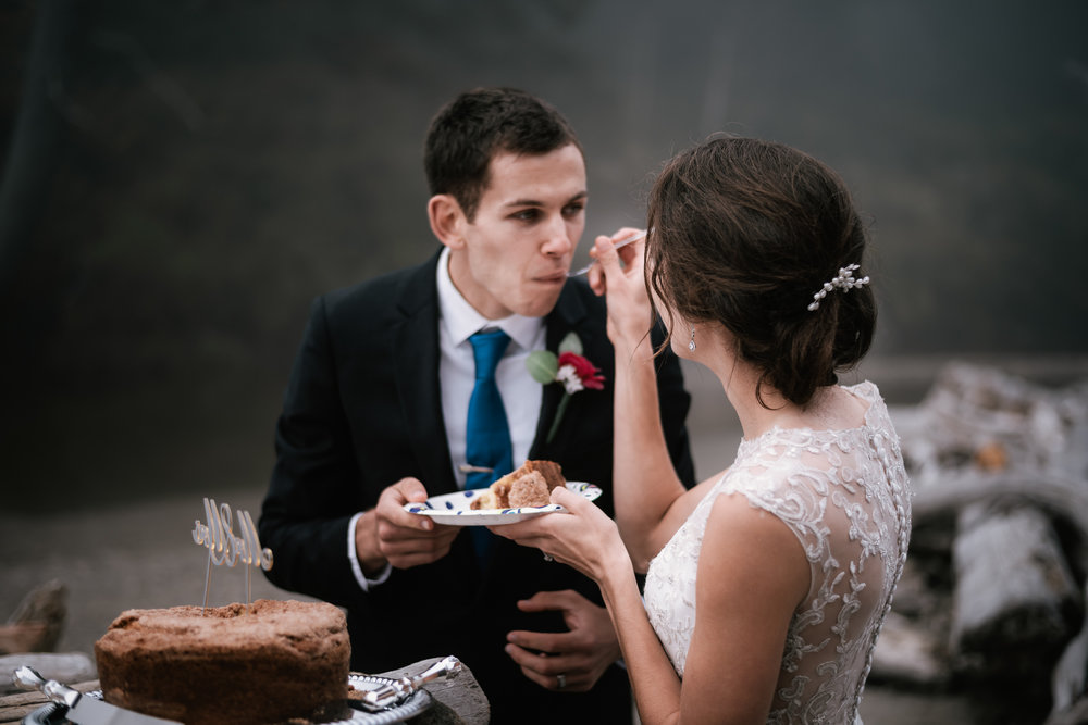 Bride feeds her new husband a piece of cake during their beachfront wedding reception in Washington.