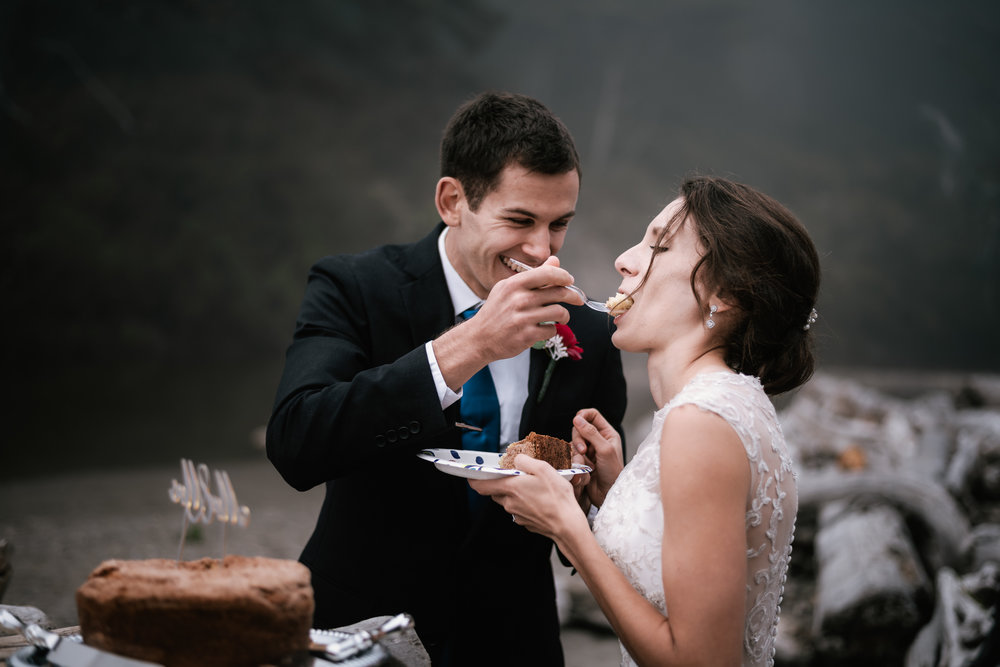 Groom gives his new wife a big bite of wedding cake.