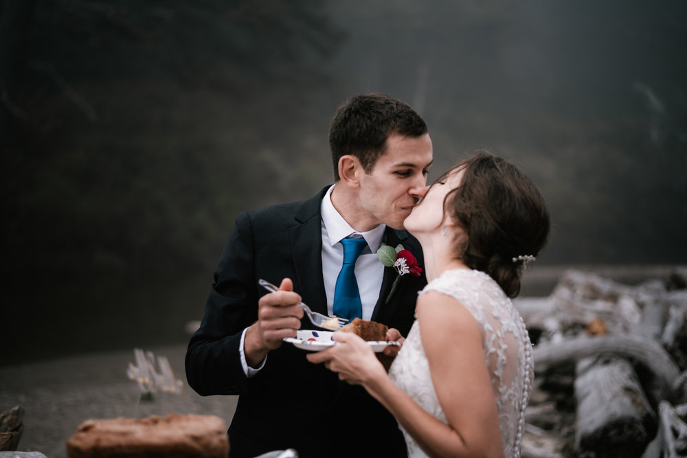 Couple kisses after their cake cutting ceremony on the foggy shoreline of Ruby Beach.