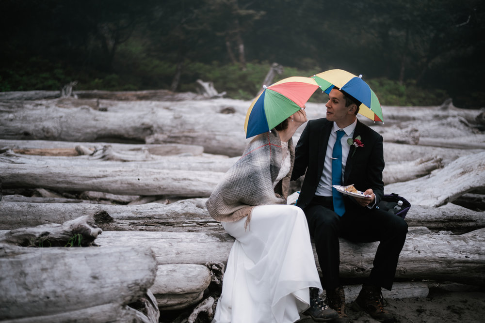 Newlyweds wearing umbrella hats to protect them from the rain makes for a cute photo.