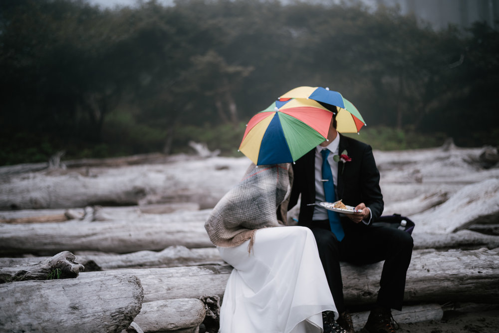 Couple kisses under their umbrella hats while sitting on the driftwood of Ruby Beach.