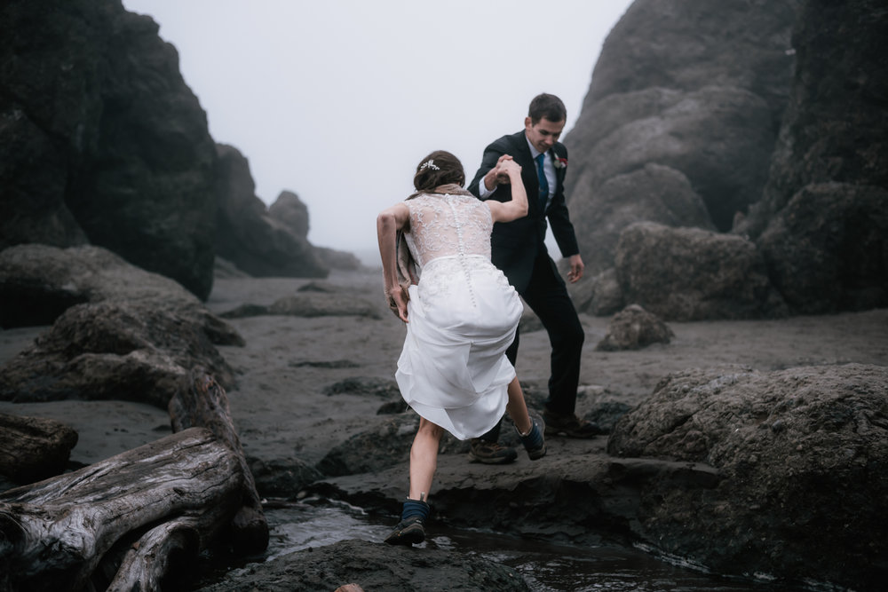 Adventurous bride hikes up her wedding dress to cross a creek at Ruby Beach.
