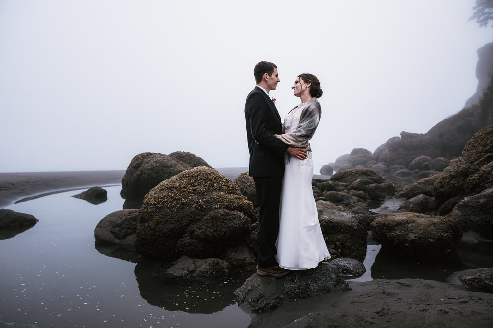 Newly married couple poses next to a tide pool in the foggy coastline of Washington.