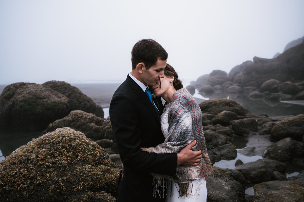 Among the barnacle covered rocks and thick fog, a couple holds each other tightly and shares a quiet moment.
