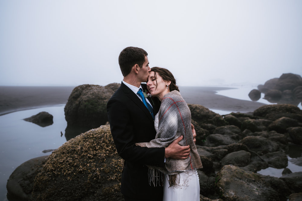 Loving groom gives his new wife a tender kiss on the forehead at Ruby Beach.