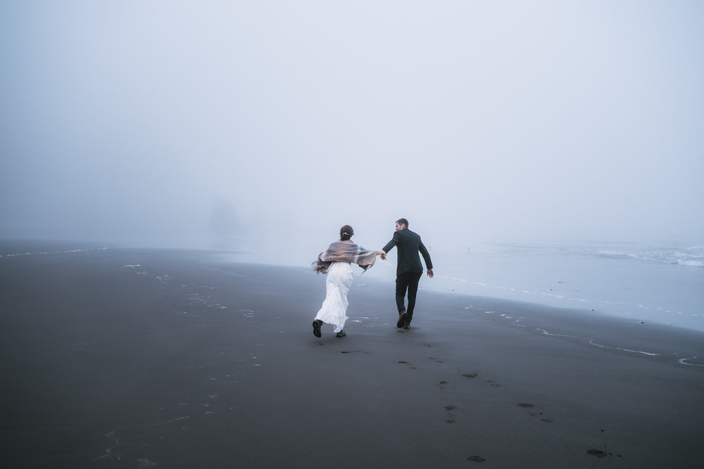 Newlyweds run down the black sand of Ruby Beach in Washington.