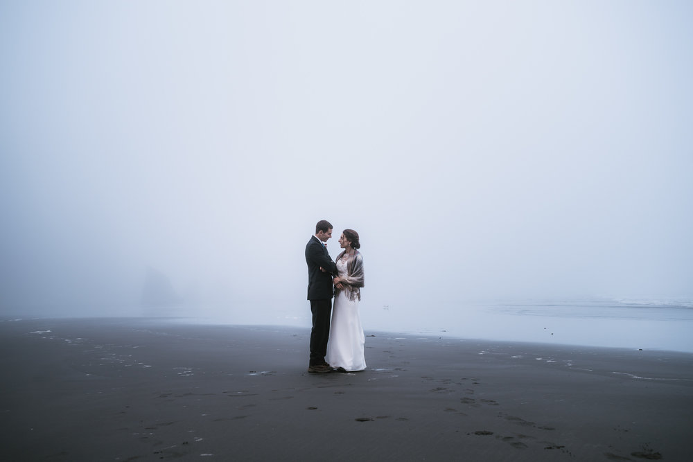 Couple stands on the black sandy beach as the fog blankets the horizon.