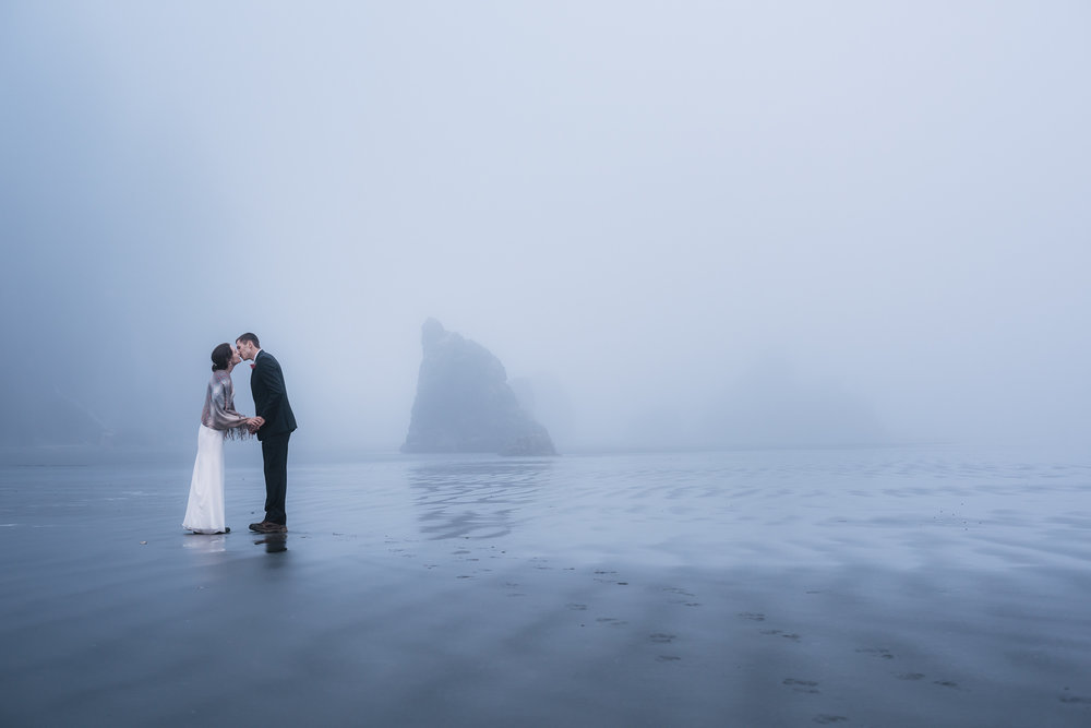 Wet sand and fog make a perfect backdrop for romantic wedding photos on the Washington coast.