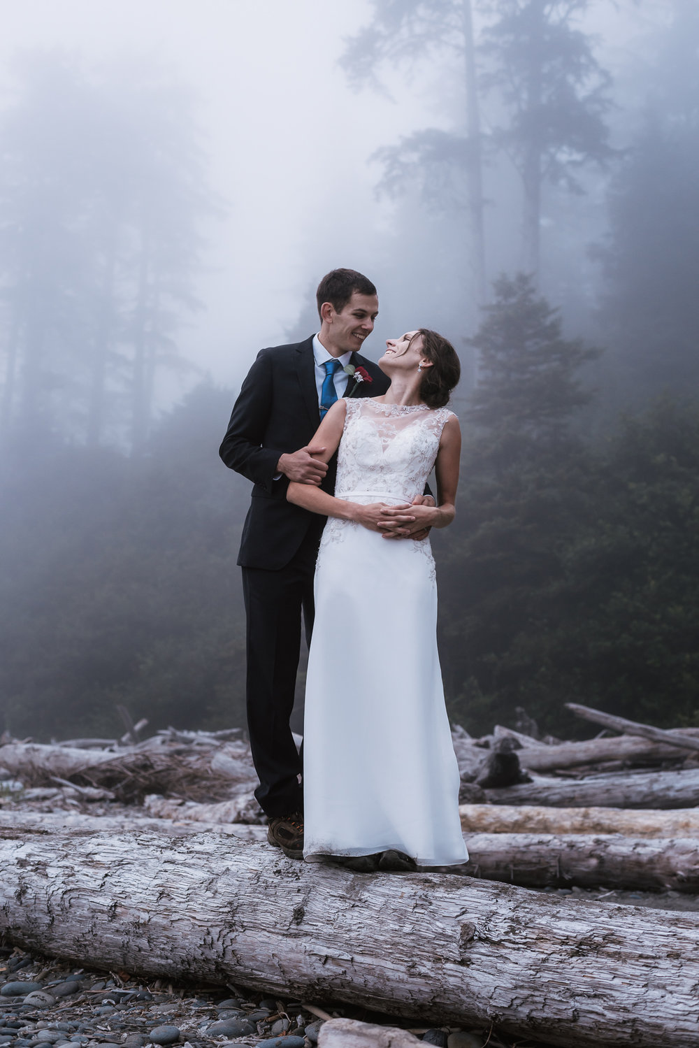 Couple stands on an old piece of driftwood and stares deeply into each other's eyes.