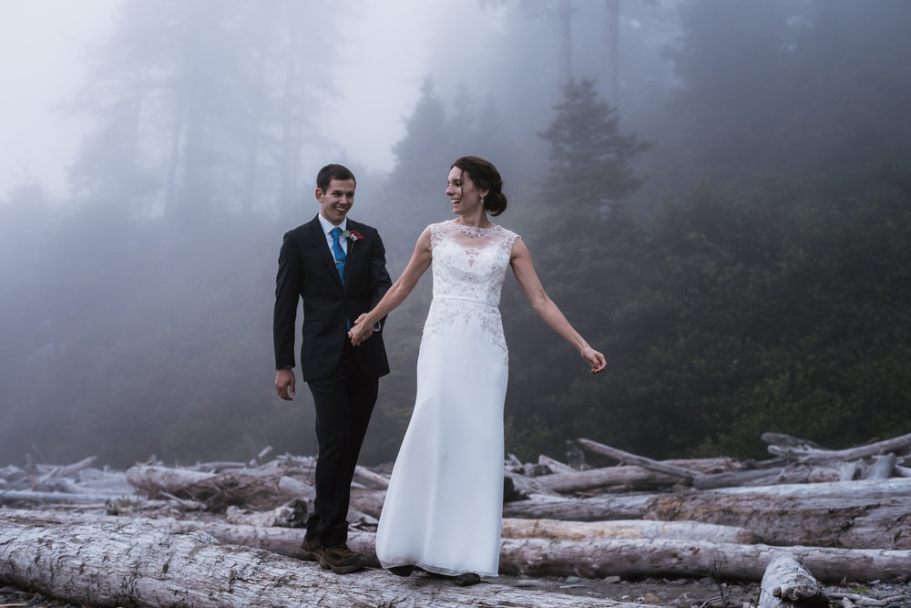 Groom follows his new bride as they walk across a log.