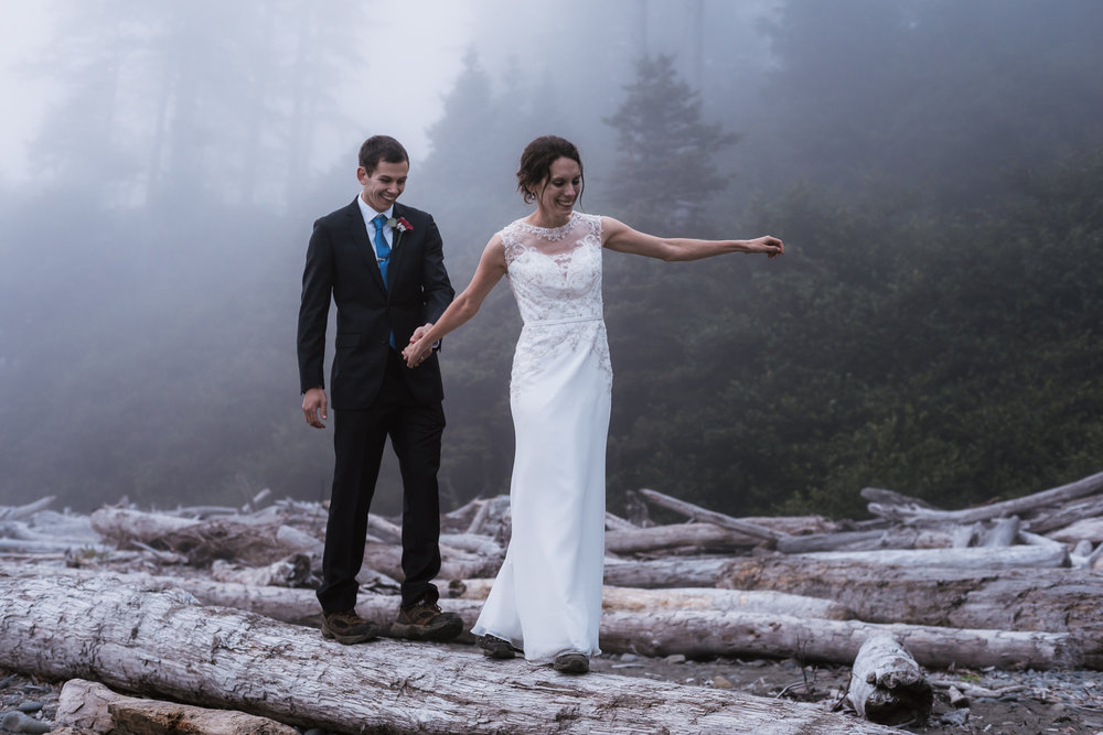 Adventurous couple balances on a log in their formal wedding attire.