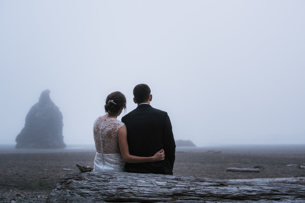 Newlyweds get close and sit on an old log and stare off into the foggy horizon Ruby Beach.