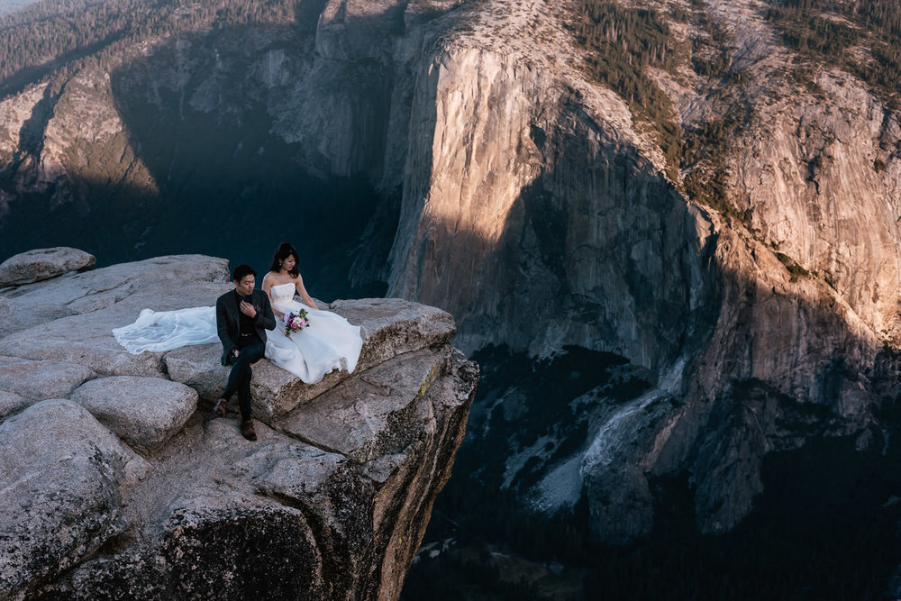 Couple sits on the cliffs and watches the sun rise over the Yosemite Valley.
