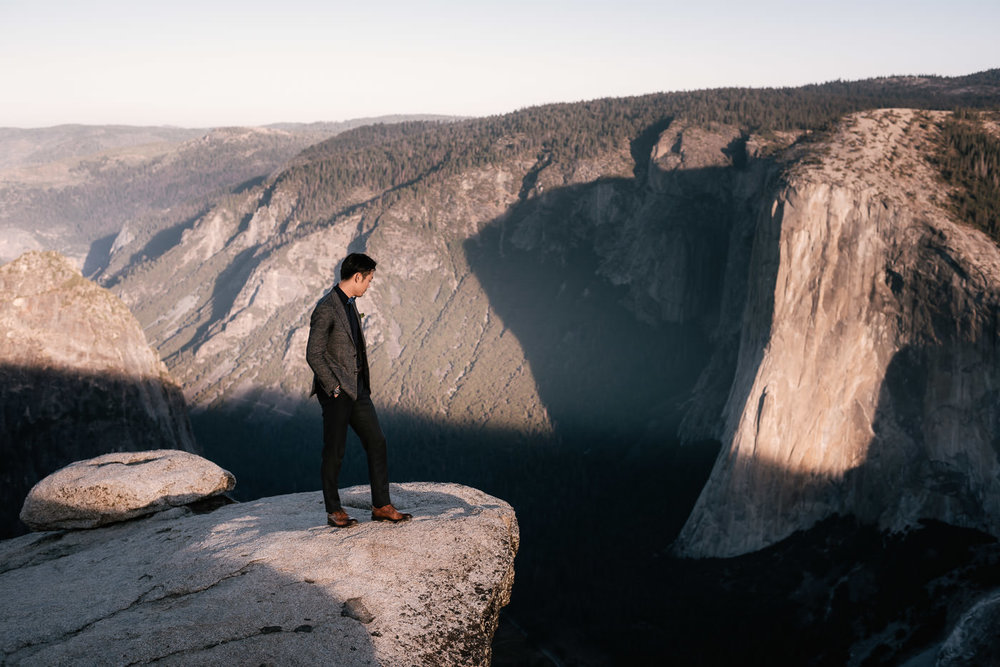 Eloping groom stands on the granite cliff and looks out over the beautiful landscape.