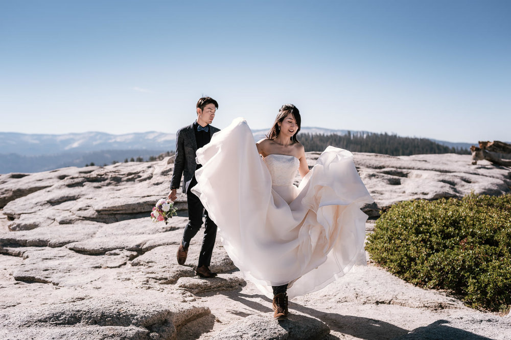 Bride and Groom trek across the granite landscape of Yosemite.