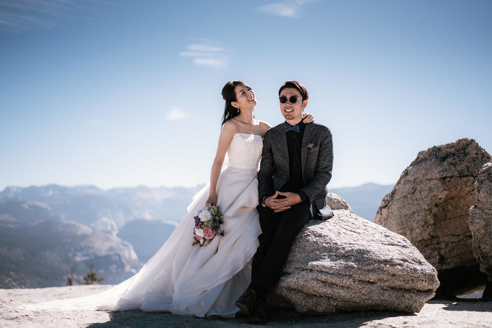 Loving pair sits on a granite boulder and smiles in their wedding clothes.