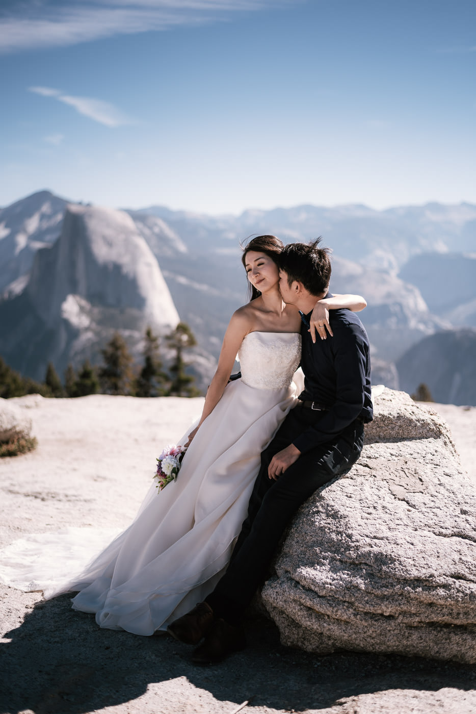 Wedding photographer captures groom as he kisses his new wife's neck as she smiles.