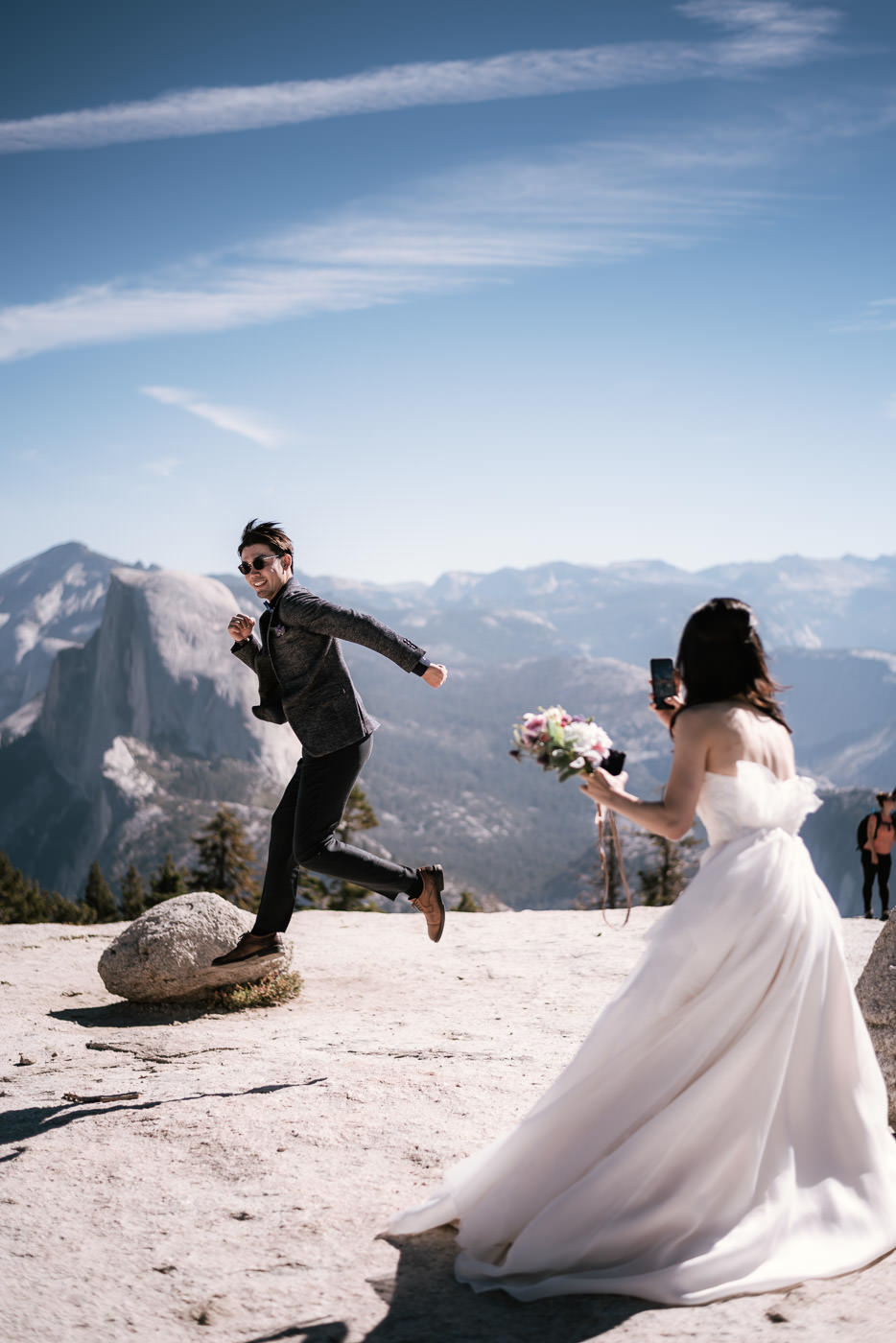 Bride captures a picture of her new husband jumping in front of Half Dome.