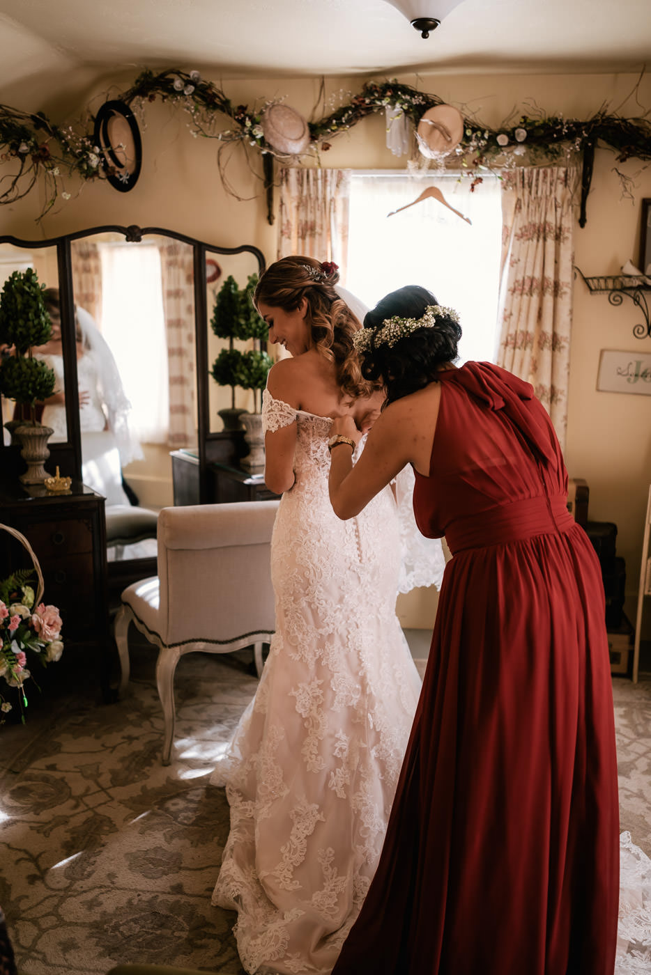 Maid of Honor helps bride put on her wedding dress for her big day.