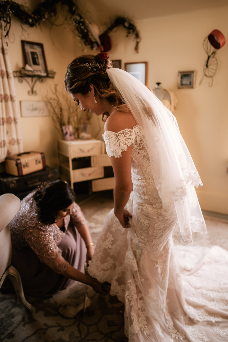 Bride's mother helps her with her heels.